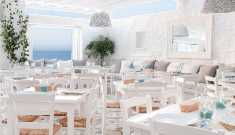 Traditional whitewashed tables and chairs in Avli restaurant at Minois Village Hotel Suites and Spa.