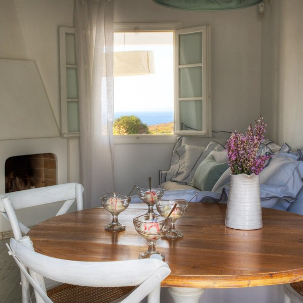 Round wooden table with ice cream, flowers & chairs in 4 People Villa, Minois Village Hotel, Paros.