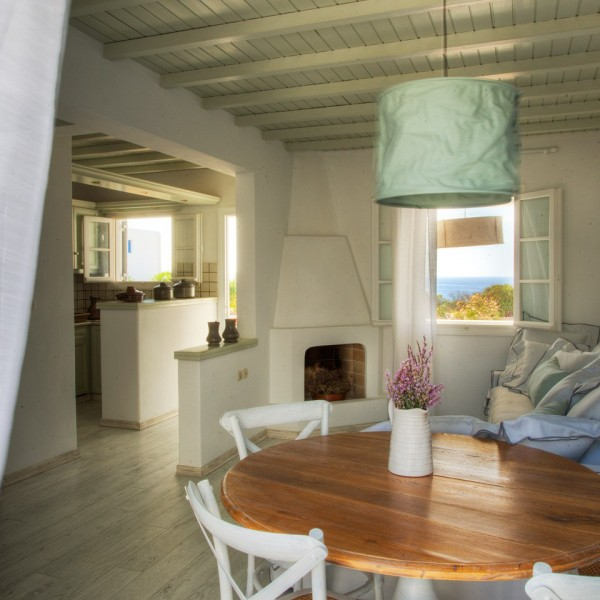 Simple traditional decor in Minois Village 4 People Villa, Paros. Round table with flowers & sofa.