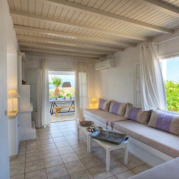 Wall clock, lamp & seating area with tables in Minois Village Hotel Suites 6 People Villa, Paros.