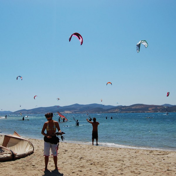 The Aegean sea by Parasporos beach is full of kite surfers practicing in the summer sun.
