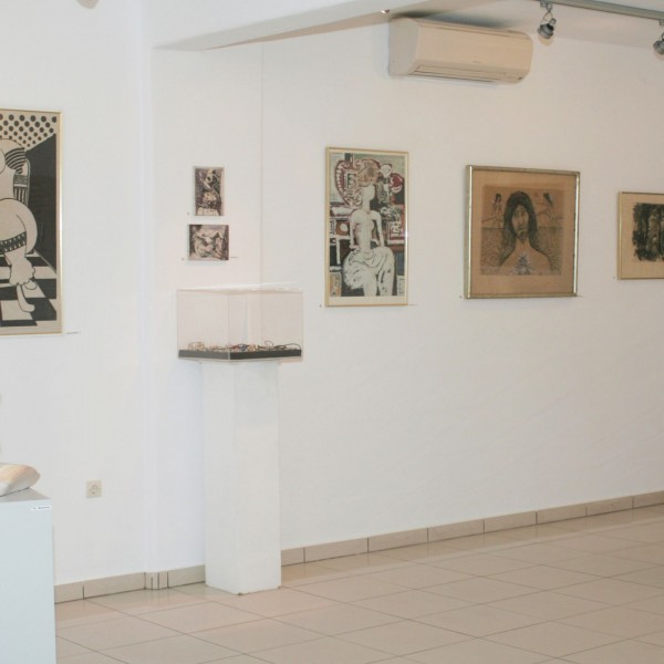 Range of different styles of paintings hung at Minois Village Art Gallery, with abstract sculptures.
