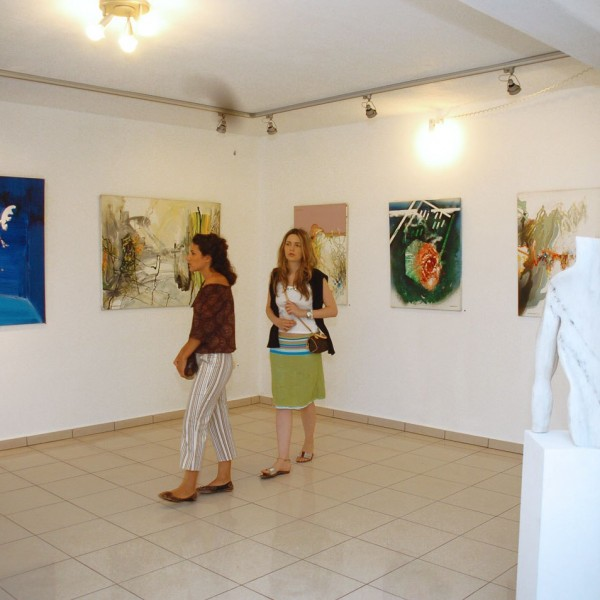 Women admire paintings displayed in Minois Village Hotel Suites & Spa Art Gallery in Paros.