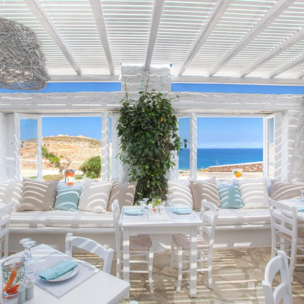 Avli restaurant seating and tables with sea and countryside view at Minois Village Hotel Suites, Paros. (Description