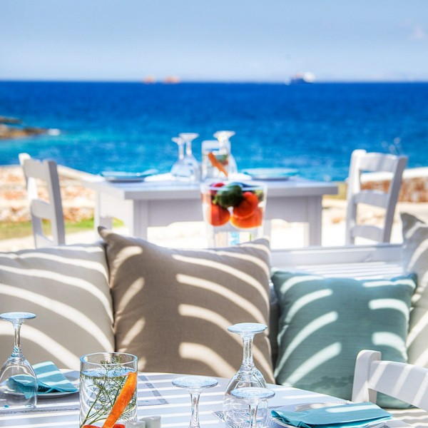 Table with wine glasses, plates & napkins, with Aegean sea view. Avli restaurant at Minois Village.