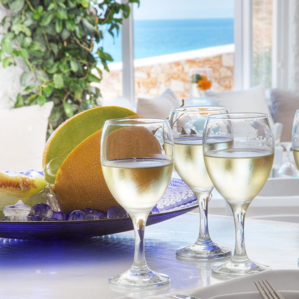 3 white wine glasses & melon on Avli restaurant table, Minois Village, Paros. View of sea behind.