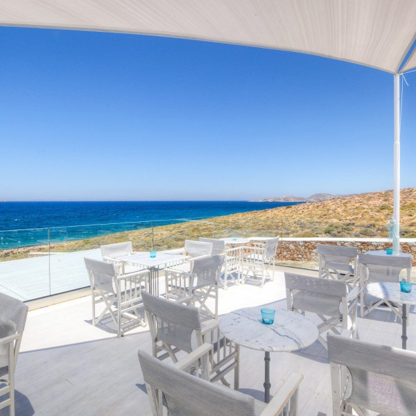 Daytime view from Deck Lounge bar at Minois Village Suites. Azure blue sea and Paros countryside.