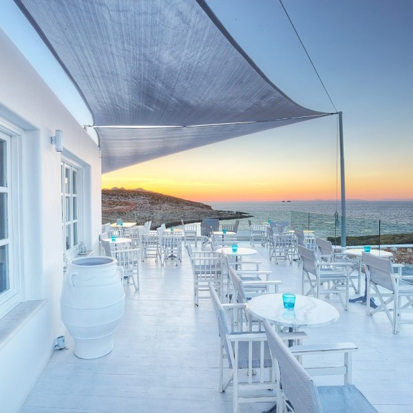 Simple white decor of Minois Village Hotel Deck Lounge bar, Paros. Chairs, marble tables, & candles.