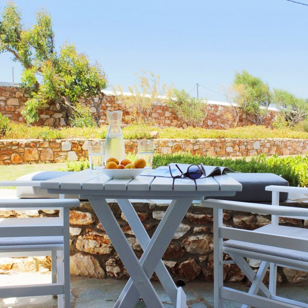Water jug, peaches, sunglasses on table with chairs & view of garden. Superior Family Studio, Paros.