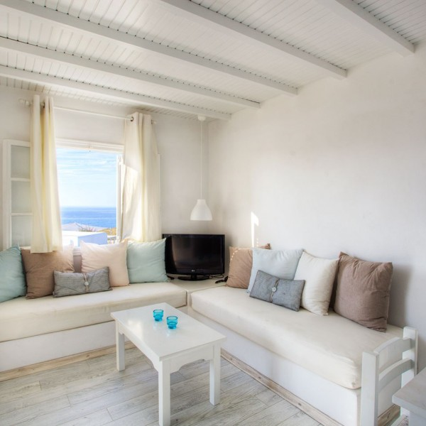 Corner sofa, TV, open windows, in Minois Village Superior First Floor Sea View Suite, Paros.