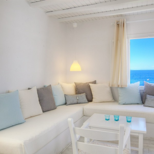 L Sofa, lamp, table, chairs & window in Minois Village Grand Superior Ground Floor Sea View Suite.