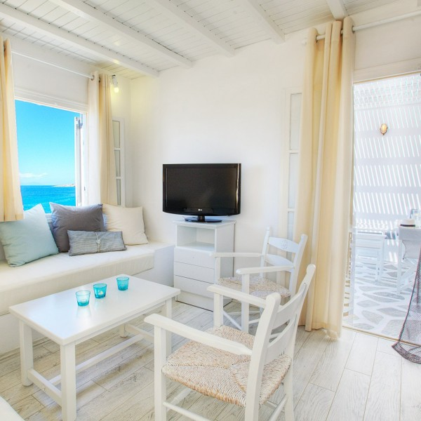 Door to balcony, TV, white sofa, table & chairs in Minois Grand Superior Ground Floor Sea View Suite