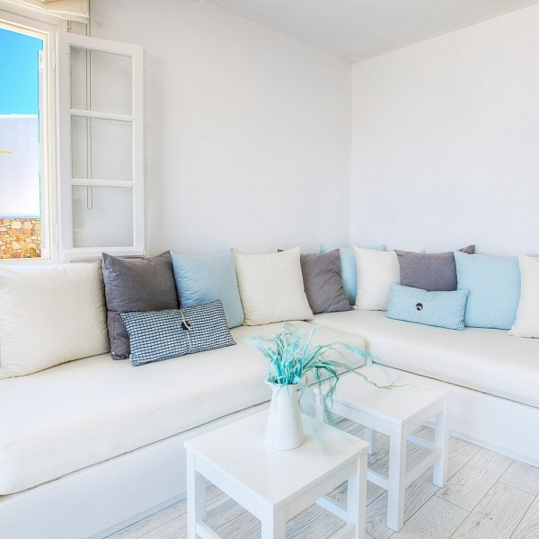 White corner sofa, tables, window, Grand Superior Ground Floor Sea View Suite, Minois Village, Paros