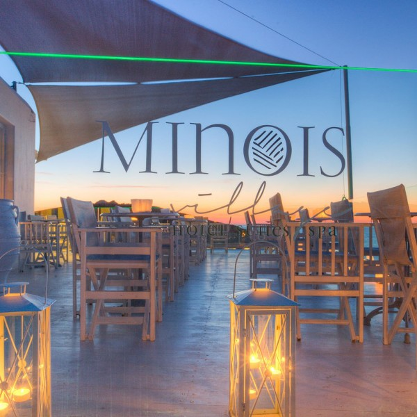 Close up view of Minois Village logo etched on glass wall with Deck Lounge Bar lit by candles behind