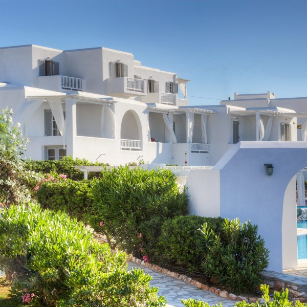 Shrubbery, pool through archway, and accommodation residences of Minois Village Hotel Suites, Paros.