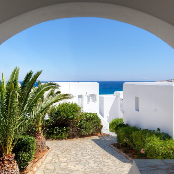 Archway looking through to Minois Village Hotel Suites accommodation residences, palm trees and sea.