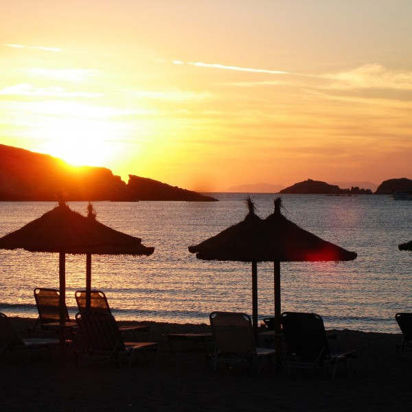 Sunset over the Aegean sea, with sunbeds & umbrella on Parasporos Beach on Paros Island.