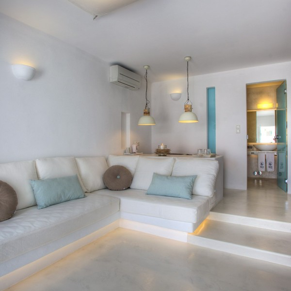 View of lounge area in Superior Ground Floor Pool View Suite, Paros. Sofa, pillows, table & bathroom
