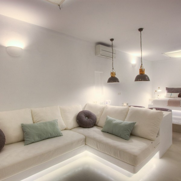 L-shaped sofa with mood lights & double bed in Minois Village Hotel Suite, in Paros.