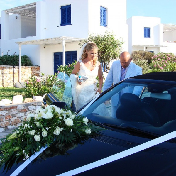 Bride climbs into car decorated with ribbons outside Minois Village Hotel Suites in Paros.