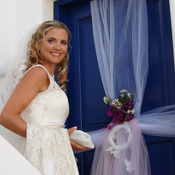 Bride smiles next to blue door after wedding at Minois Village Hotel Suites and Spa in Paros.