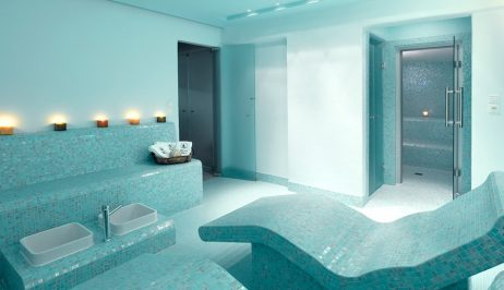 Spa room at Minois Village Hotel Suites and Spa. Turquoise mosaic tiles and chair and row of candles