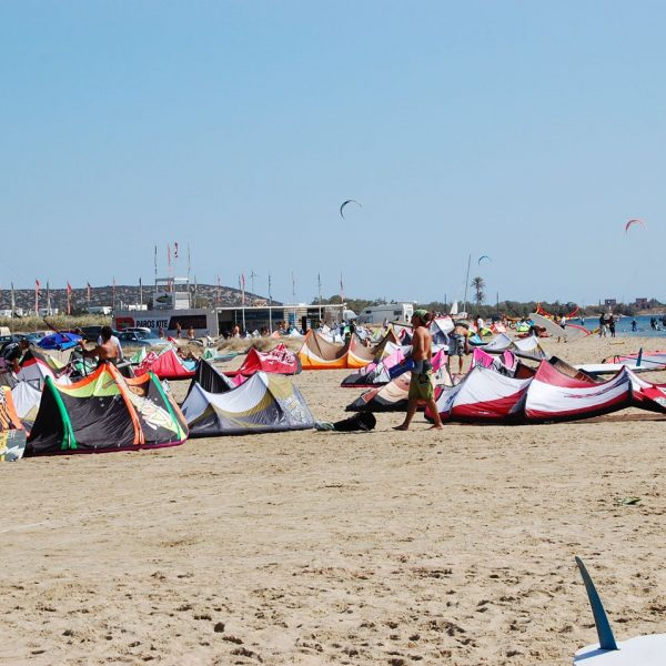 Kites rest on the sand at Parasporos beach. In the background, kite surfers practice in the sea.