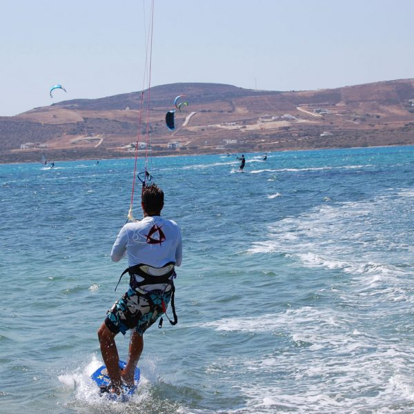 Man kite surfing in the clear waters of the Aegean sea off Parasporos beach, Paros.