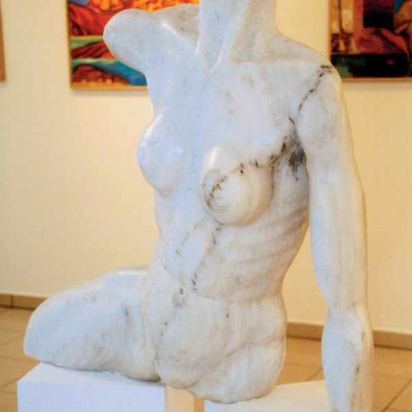 Close up of female sculpture at Minois Village Suites Art Gallery, Paros. Paintings in background.