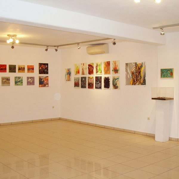 Modern art paintings hung on the wall of the Art Gallery in Minois Village Hotel Suites & Spa, Paros