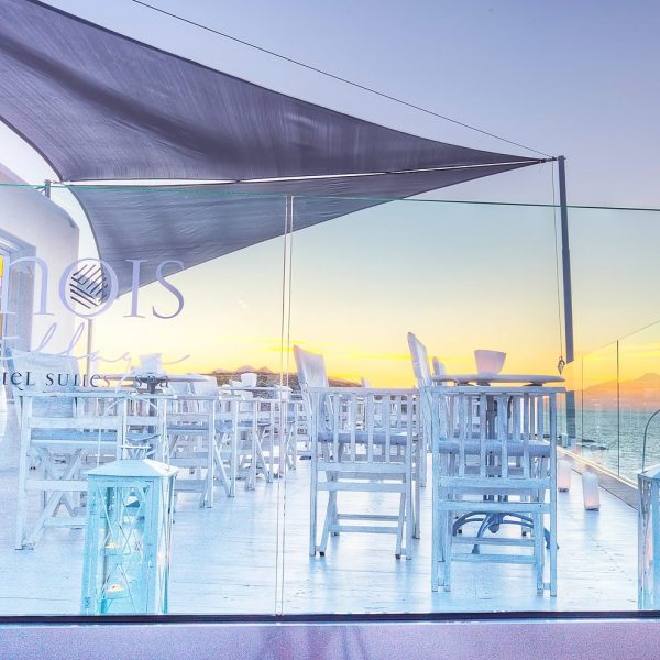 Deck lounge bar and sunset viewed through Minois Village Hotel Suites and Spa Logo, Paros.