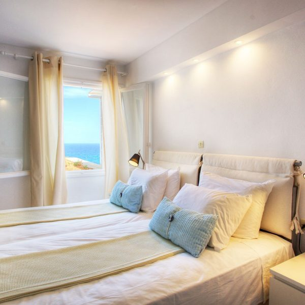 Bedside table & lamp, double bed, & open window, Minois Village Superior First Floor Sea View Suite.
