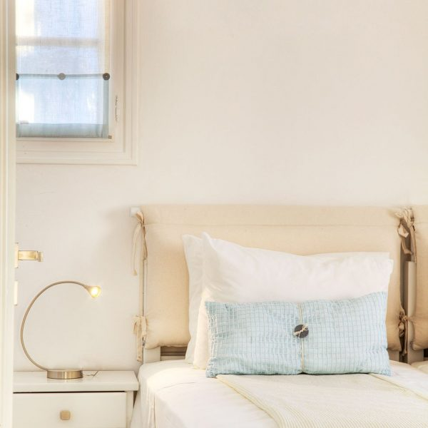 Modern bedside lamp on table. Double bed in Minois Village Superior First Floor Sea View Suite Paros