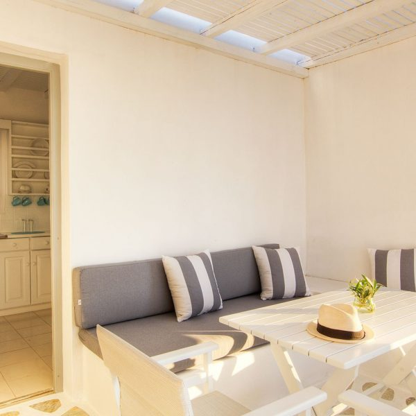Hat on table, with sofa & view of kitchen, Minois Village Superior First Floor Sea View Suite, Paros