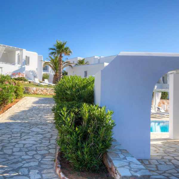 The accommodation residences of Minois Village Hotel Suites and Spa in Paros, with tree lined path.