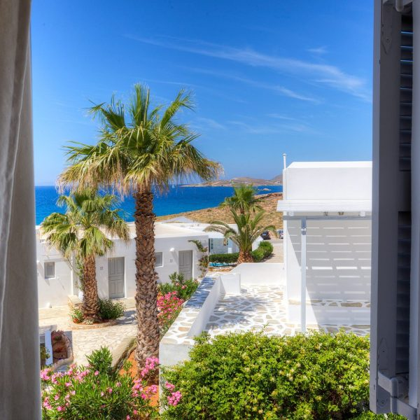 Palm trees and sea viewed through open window in Minois Village Hotel Suites and Spa, Paros.