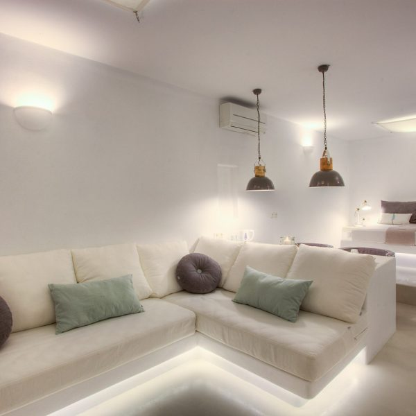 Sofa, lights, kettle & double bed in Minois Village Superior Ground Floor Pool View Suite, Paros.
