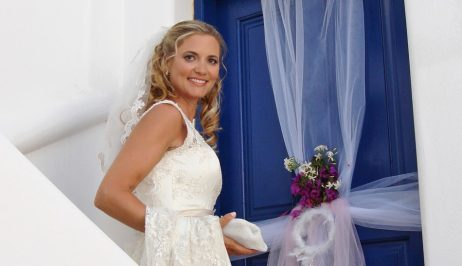 Smiling blonde bride beside traditional blue door decorated with ribbons after wedding in Paros.