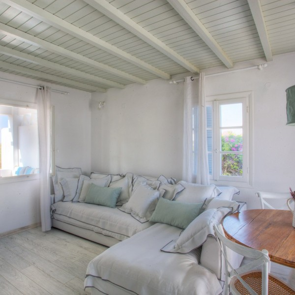 Wooden table with flowers, & large sofa with cushions in Minois Village 4 People Villa, Paros.