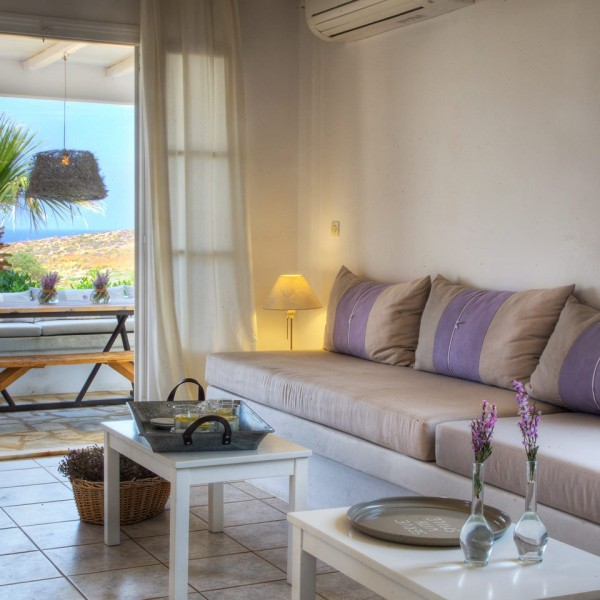 Trays on tables with sofas in Minois Village 6 People Villa, Paros. Veranda with palm tree view.