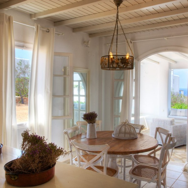 Worktop with flowers, round table & chairs in 6 People Villa, Paros. View of sea & trees.