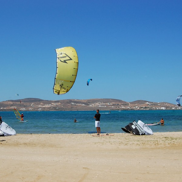 Kite surfers enjoy the Aegean sea at Parasporos beach, Paros. Blue sky & mountains in background.
