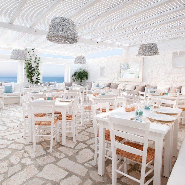 Chairs and tables arranged in Avli restaurant, Minois Village Hotel Suites, Paros. Sea in background