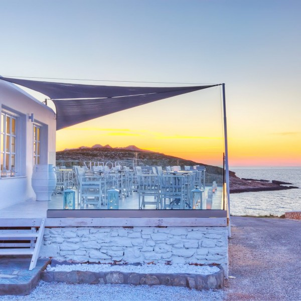 Sun sets over the Aegean sea behind the Minois Village Hotel Suites Deck Lounge Bar in Paros.