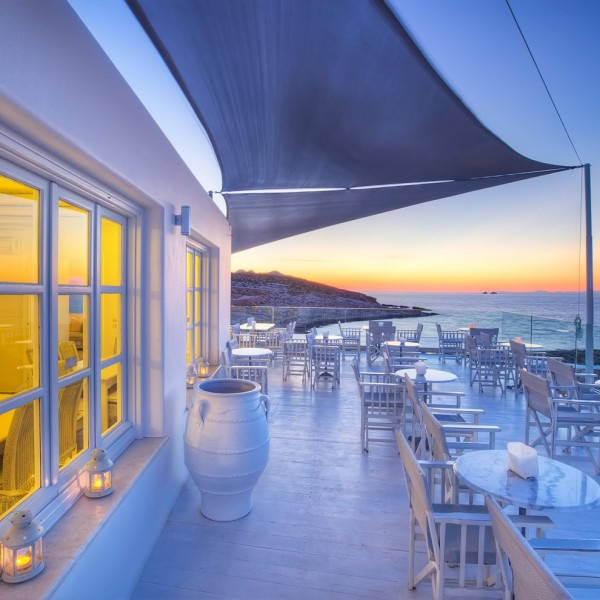 Windows, tables, and chairs of Minois Village Hotel Suites Deck Lounge bar, Paros. Sunset over sea.