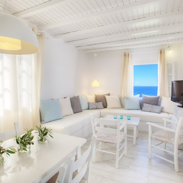 Decorated tables, chairs, TV & sofa in Minois Grand Superior Ground Floor Sea View Suite, Paros