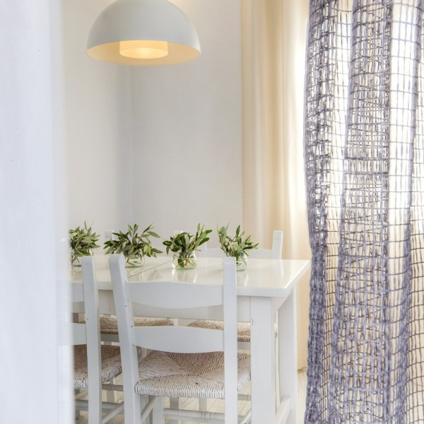 Light above wood table & chairs in Minois Village Grand Superior Ground Floor Sea View Suite, Paros