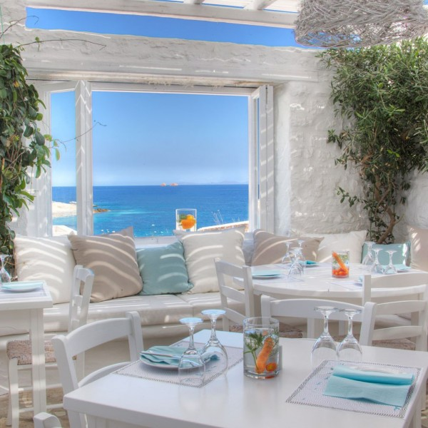Avli restaurant at the Minois Village Hotel Suites. Table set for meal, view of the Aegean sea.
