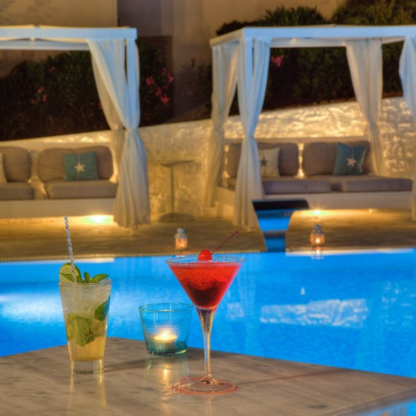 Night time photo of drinks beside pool of Minois Village Hotel Suites. Sofas under awnings behind.