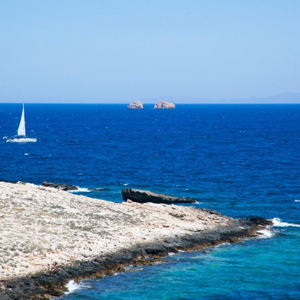 Sailing boat on the Aegean sea. Paros coastline can be seen, and two rocks on the horizon.